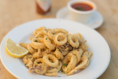 Fried calamari served with a side of marinara sauce.